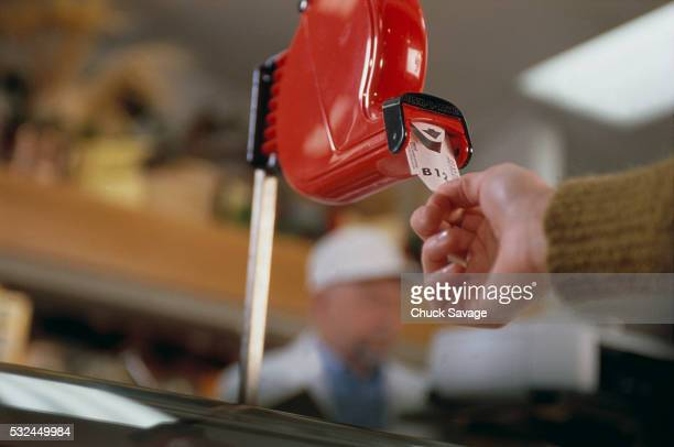 woman taking a number in deli - delicatessen stock pictures, royalty-free photos & images