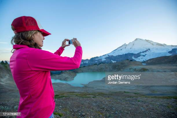 a woman taking a phone photo while hiking in the mountains. - bellingham stock pictures, royalty-free photos & images