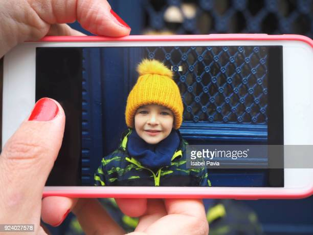 Woman taking a phone picture of a boy