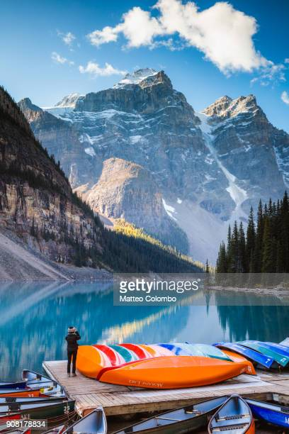 woman taking a photo at moraine lake in autumn - canadian rockies stockfoto's en -beelden