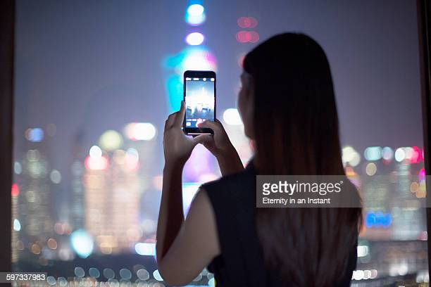 Woman taking a photo at night of the city