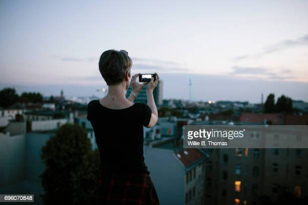 A Woman Taking A Photo From A Rooftop