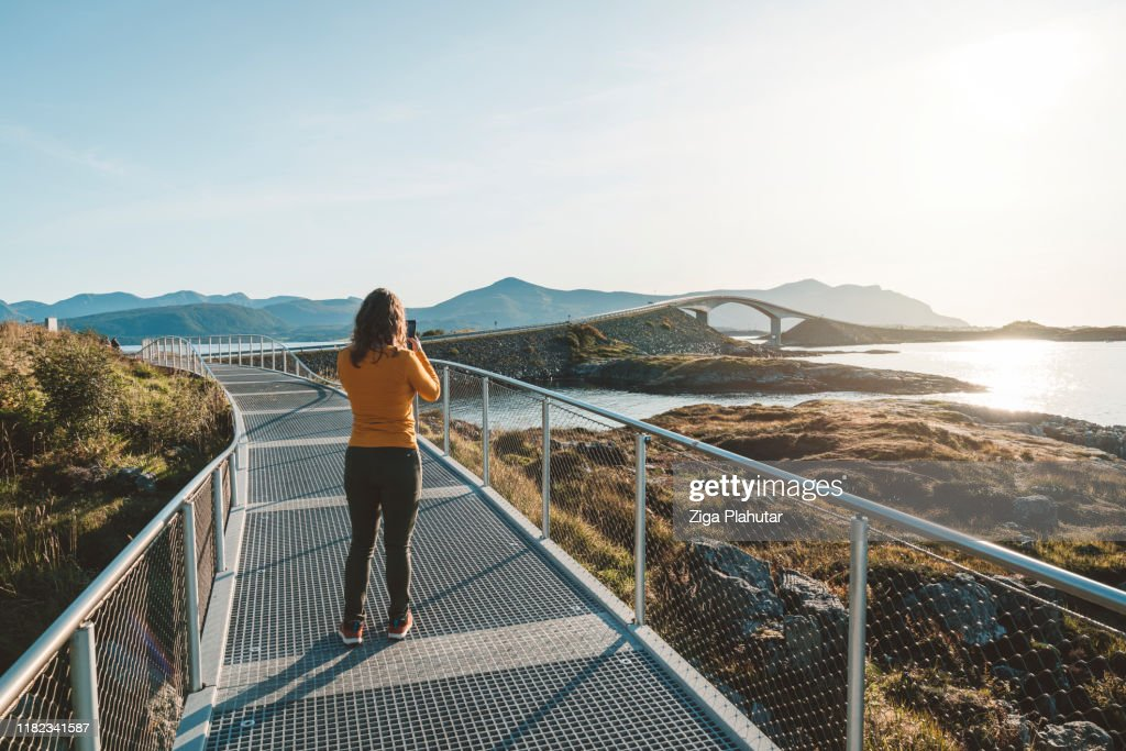 Woman taking a photo of Atlantic road in the distance : Stock Photo