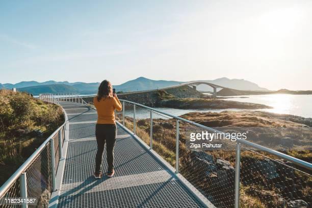 femme prenant une photo de la route de l'atlantique dans la distance - atlantic road norway photos et images de collection
