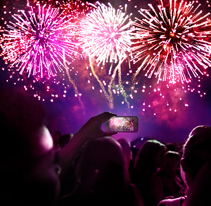 Woman taking a photo of firework display - gettyimageskorea