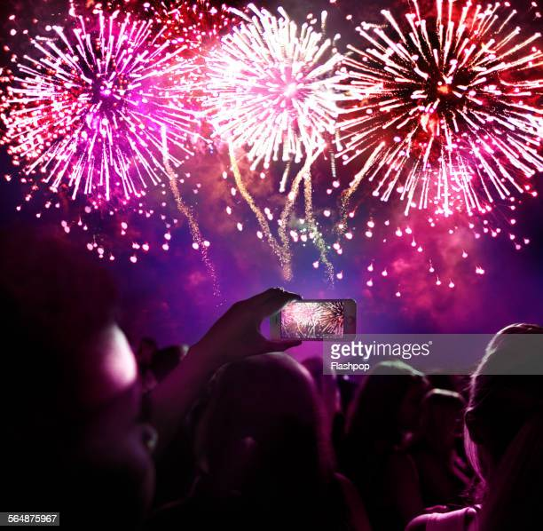 woman taking a photo of firework display - firework display stock pictures, royalty-free photos & images