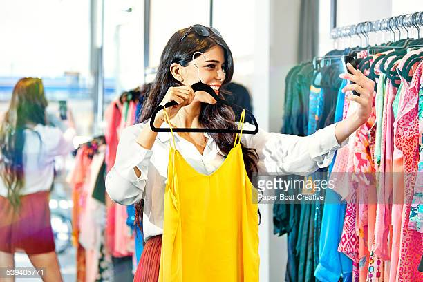 Woman taking a photo of herself with a new dress