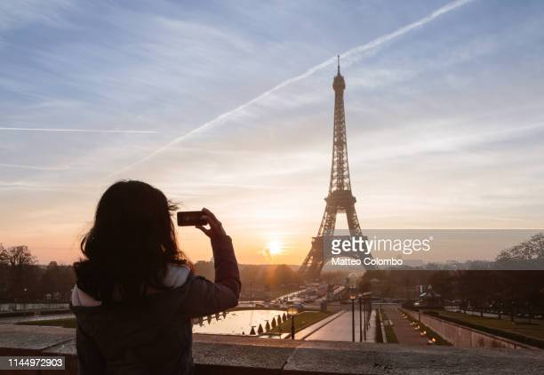 woman taking a photo of the eiffel tower, paris, france - monument stock pictures, royalty-free photos & images