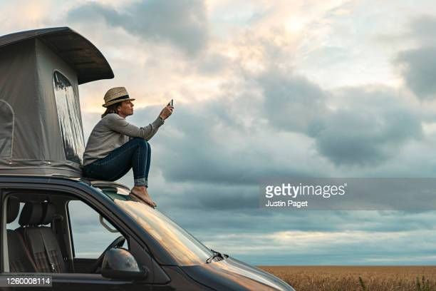 woman taking a photo whilst sitting on roof of camper at sunset - travel stock pictures, royalty-free photos & images