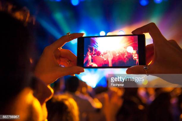 woman taking a photo with phone at music event - concert photos et images de collection