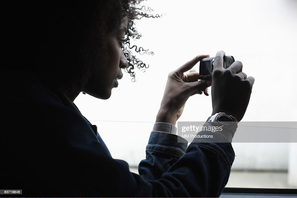 Woman taking a photograph from window : Stock Photo