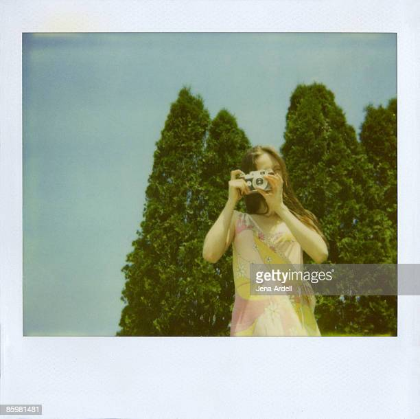 Woman taking a photograph with a vintage camera