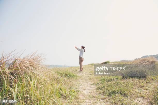 女性が海辺でスマート フォンでの写真撮影