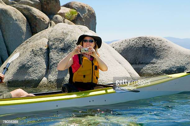 Woman taking a picture in a kayak
