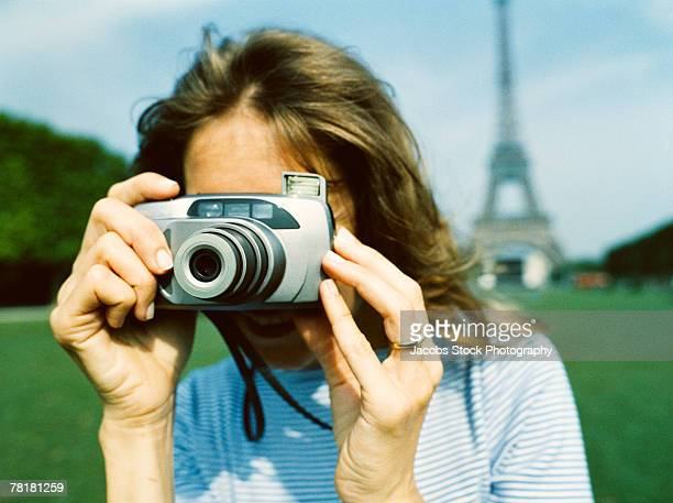 Woman taking a picture near the Eiffel Tower