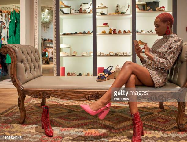 woman taking a picture of a pair of shoes with her cell phone - red dress fotografías e imágenes de stock