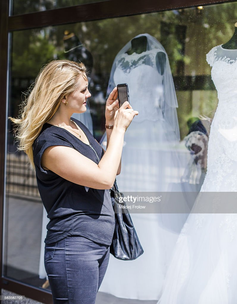 Woman taking a picture of a wedding dress : Stock Photo