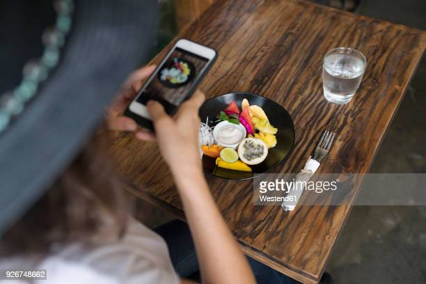 woman taking a picture of food on a plate with smartphone - influencers stock pictures, royalty-free photos & images