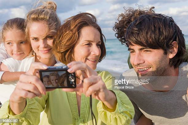 Woman taking a picture of her family with a digital camera