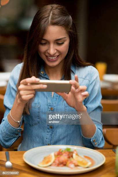 Woman taking a picture of her food at a restaurant