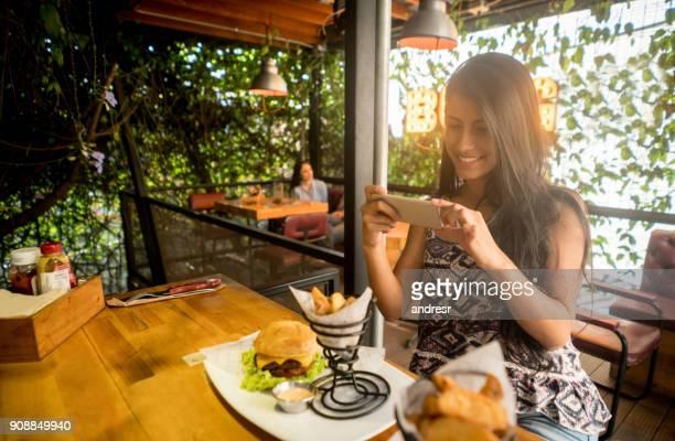 レストランで料理の写真を撮る女性 - 採点 ストックフォトと画像