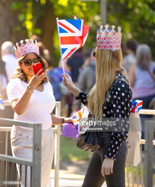 woman taking a picture of her friend while on their way to celebrate the marriage of meghan markle and prince harry at st george's chapel at windsor castle - meghan stock photos and pictures