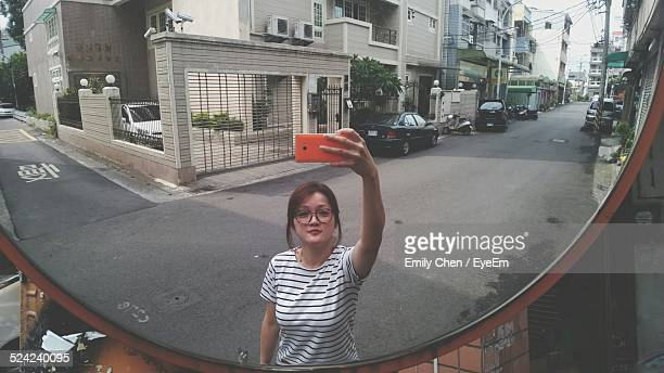 woman taking a picture of herself with a mobile phone - mirror selfie stock pictures, royalty-free photos & images