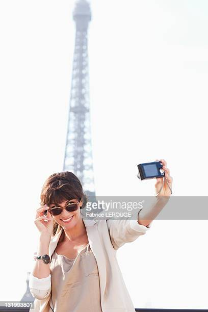 Woman taking a picture of herself with the Eiffel Tower in the background, Paris, Ile-de-France, France