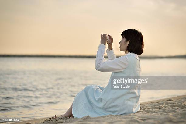 Woman taking a picture of the sea in the smartphon