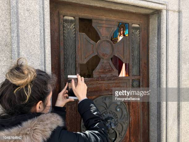 Woman taking a picture to mausoleum in cemetery