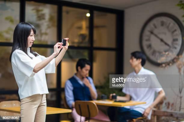 カフェのテラスからスマート フォンで写真を撮る女性