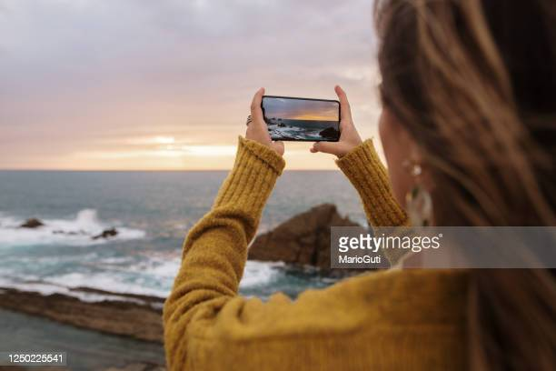 woman taking a picture with a smartphone - photography themes stock pictures, royalty-free photos & images