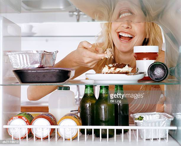 Woman Taking a Piece of Tiramisu in a Fridge With Her Finger