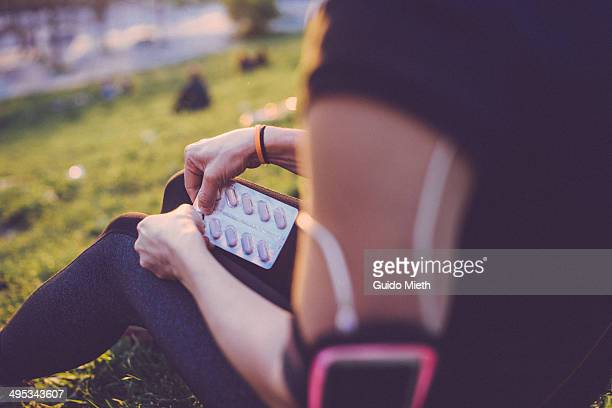 Woman taking a pill after workout.