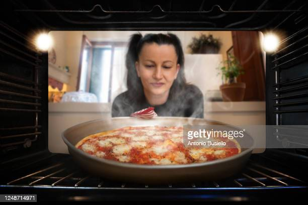 woman taking a pizza out of the oven - oven stock pictures, royalty-free photos & images