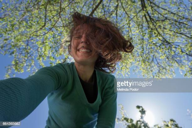 woman taking a self portrait by leaning over camera - bending over stock pictures, royalty-free photos & images