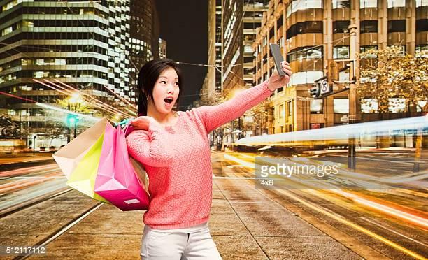 Mulher tomando um selfie na cidade à noite