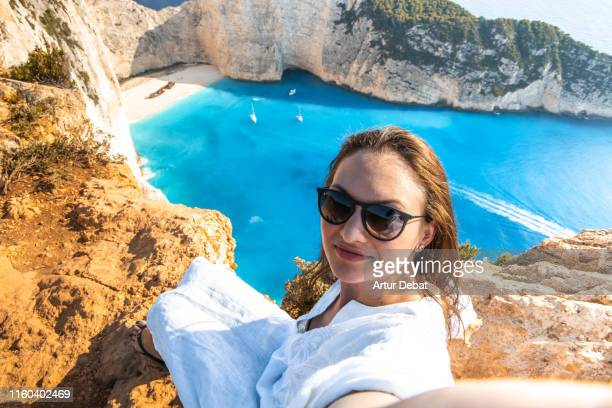 woman taking a selfie from viewpoint of the famous shipwreck beach in greece. - mar jónico fotografías e imágenes de stock