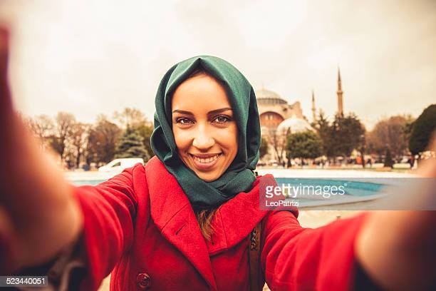 Woman taking a selfie in front of a mosque