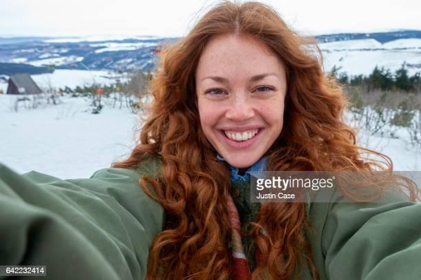 woman taking a selfie in front of beautiful winter landscape - selbstportrait stock-fotos und bilder