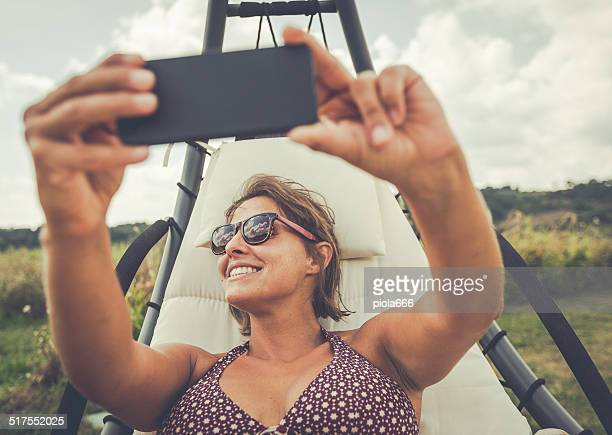 Woman taking a selfie on lounge chair