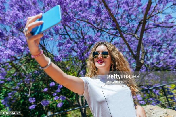 woman taking a selfie with smart phone - jacaranda tree stock pictures, royalty-free photos & images