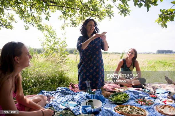 Woman taking a smartphone photo of a picnic