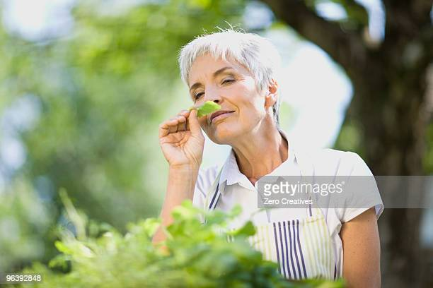woman taking a smell at some herbs
