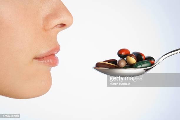 Mujer tomando una cucharada de pastillas