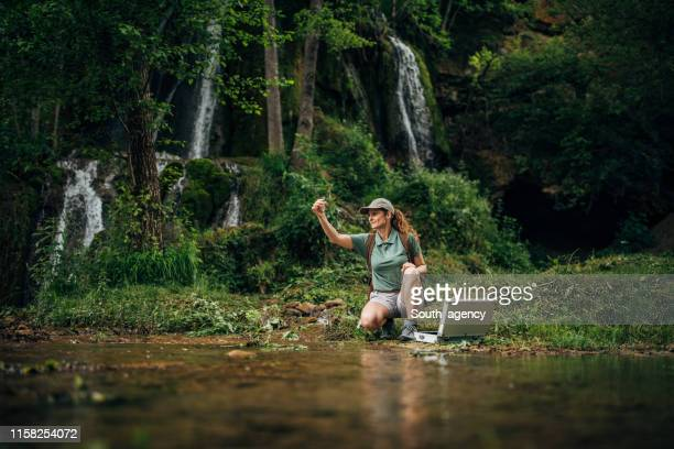 woman taking a water sample - environmentalist stock pictures, royalty-free photos & images