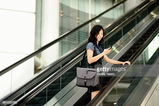 A woman taking an escalator up to work