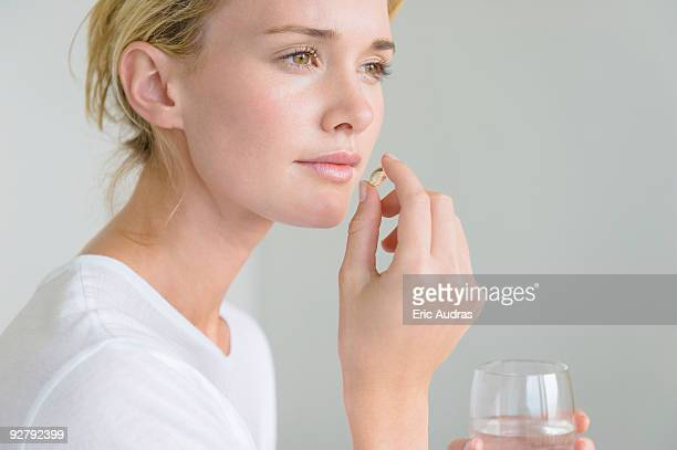 woman taking an omega-3 capsule - nutritional supplement stock pictures, royalty-free photos & images