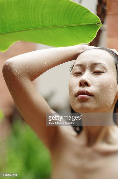 Woman taking an outdoor shower, eyes closed