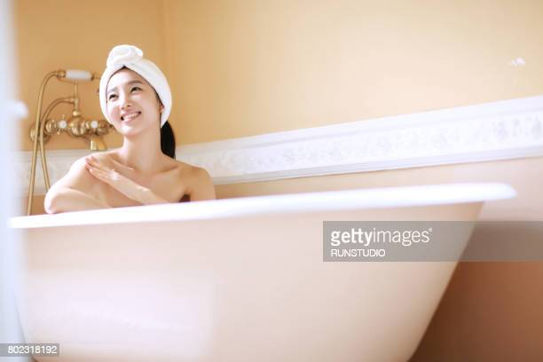 woman taking bath in modern bathroom
